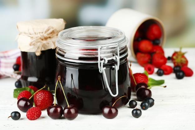 나무 테이블에 유리 항아리에 딸기와 맛있는 잼