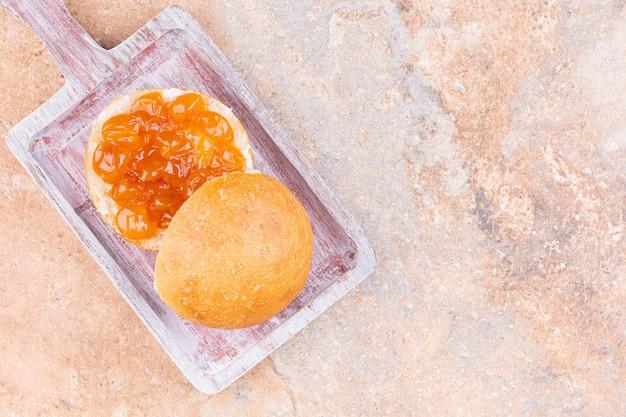 大理石の背景に、ボード上のパンとおいしいジャム。