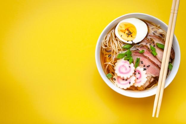 흰색 세라믹 그릇에 담긴 맛있는 일본 국수 라면, 고기 국물, 얇게 썬 돼지고기, 나루토마키, 파스텔 노란색 배경에 노른자가 있는 계란. 일본의 전통 요리, 위쪽 전망, 클로즈업, 텍스트 공간