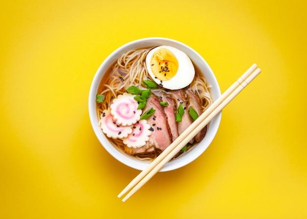 파스텔 노란색 배경에 고기 국물, 얇게 썬 돼지고기, 나루토마키, 달걀 노른자가 있는 흰색 세라믹 그릇에 맛있는 일본 국수 라면. 일본의 전통 요리, 평면도, 클로즈업, 개념