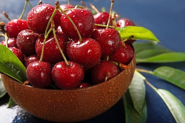 Вкусные сочные вишни на тарелку. капли воды на вишне. крупный план