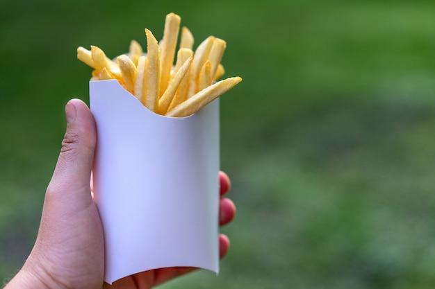 男のホワイトペーパーボックスでおいしいジューシーなフライドポテトは、屋外の自然に手します。ファーストフードのモックアップongreen背景。本文の空き領域を持つ不健康な食品のコンセプト。フライドポテトメニュー。