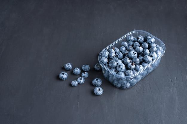 黒く暗い背景のプラスチック容器においしいジューシーな生のブルーベリー。店の棚にあるスーパーマーケットでのベリーの包装。