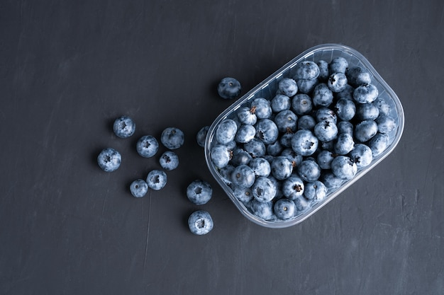 Tasty juicy raw blueberries in a plastic container