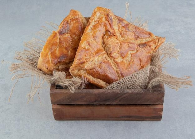 Вкусная выпечка хачапури в деревянной коробке.
