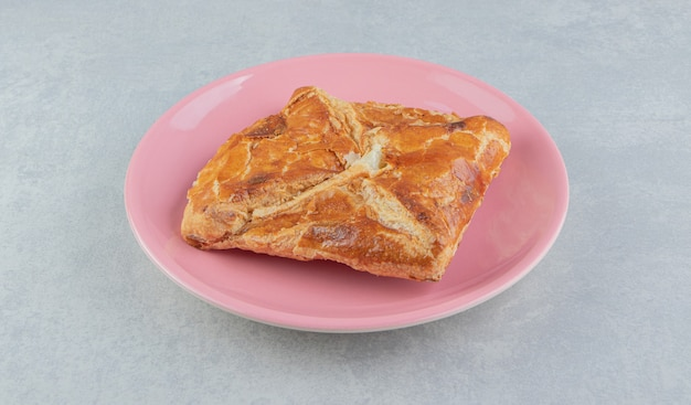 Вкусное тесто хачапури на розовой тарелке.