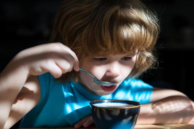 おいしい子供たちの朝食健康的な家庭料理の男の子は子供のための台所の栄養で食べる