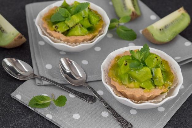 Вкусные тарталетки киви на сером столе. летний десерт