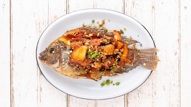 Вкусная большая жареная нильская рыба тилапия с чили и чесноком в овальной керамической тарелке на белом фоне деревянной текстуры, вид сверху, соотношение сторон full hd, 16 x 9