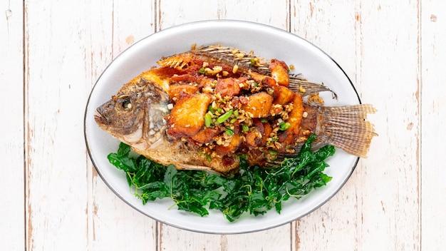Вкусная большая жареная нильская рыба тилапия с чили, чесноком и хрустящими листьями базилика в овальной керамической тарелке на белом фоне деревянной текстуры, вид сверху