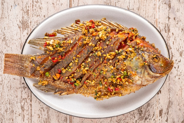 Tasty large fried nile tilapia fish with chili, garlic and coriander in oval ceramic plate on white wooden texture background, top view
