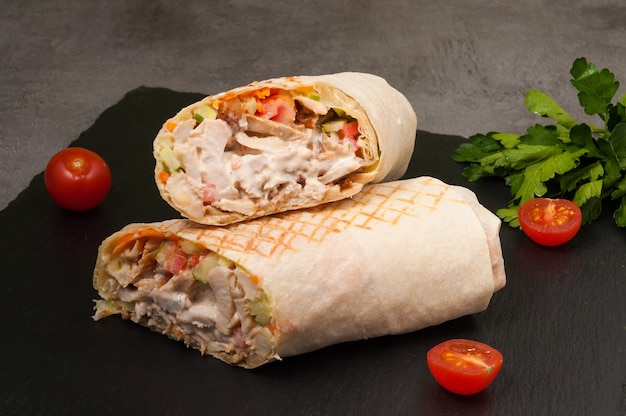 Tasty large shawarma with vegetables and chicken on a dark background