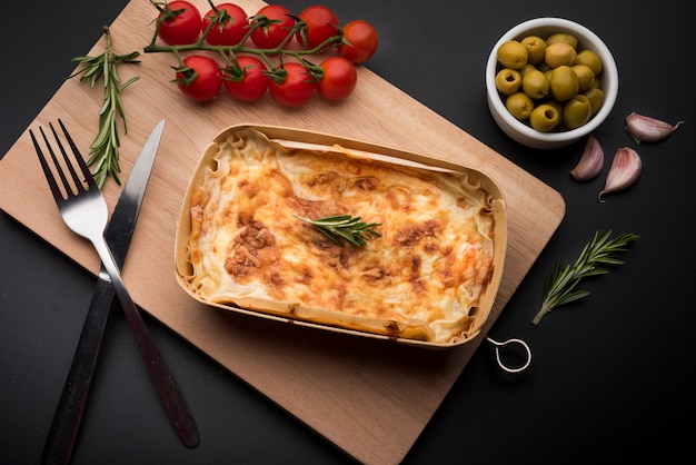 Tasty lasagna and ingredient on wooden cutting board over black surface