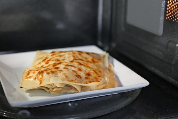 Tasty lasagna on plate in microwave