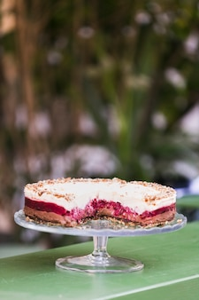Tasty layer cake on cake stand against blurred background