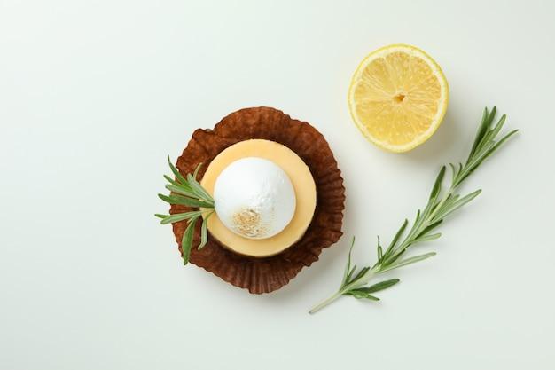 Tasty lemon cupcake on white background, top view