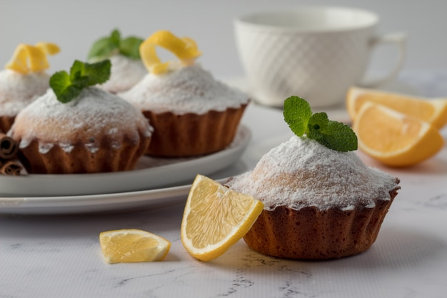 Tasty lemon muffins with sugar powder on marble table