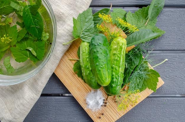 Вкусные малосольные огурцы. сезонный сбор овощей на зиму. слабосоленые огурцы вид сверху с ингредиентами по рецепту лежат на деревянной разделочной доске в деревенском стиле
