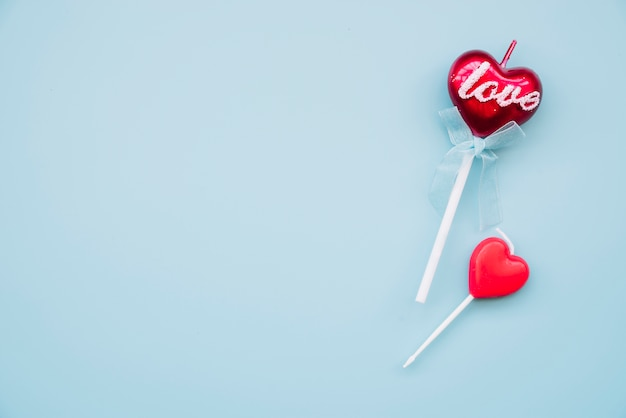 Tasty lollipop and decorative candle on wands in form of hearts