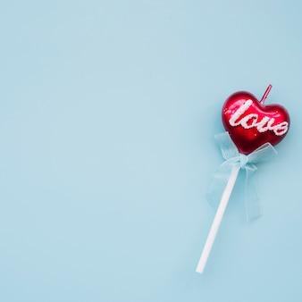 Tasty lollipop on wand in form of heart