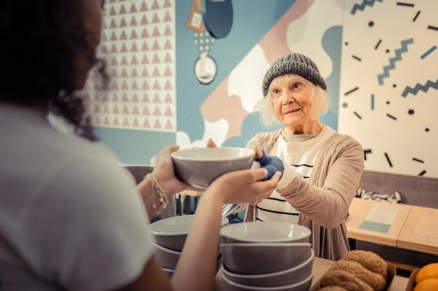 おいしいランチ。スープでボウルを取りながら若い女性を見て快適な空腹の女性