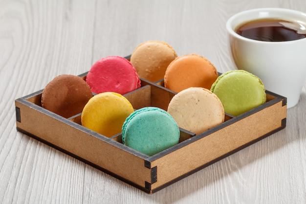 Tasty macaroons cakes of different color in brown wooden box and cup of coffee on gray boards