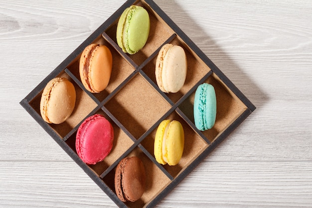Tasty macaroons cakes of different color in brown wooden box on gray boards. top view Premium Photo
