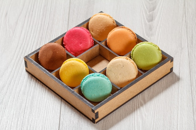 Tasty macaroons cakes of different color in brown wooden box on gray boards