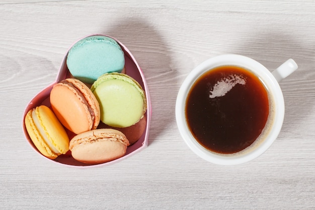 Tasty macaroons cakes of different color in cardboard box in the shape of heart and cup of coffee on gray boards. top view