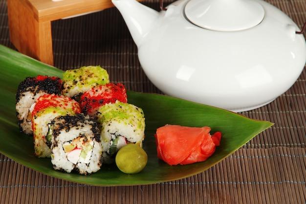 Вкусные суши маки - роллы на зеленом листе на сером