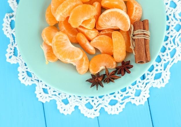 Tasty mandarine's slices on color plate on blue