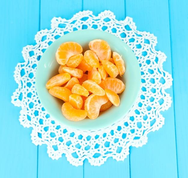 Ломтики вкусного мандарина на цветной тарелке на синей поверхности