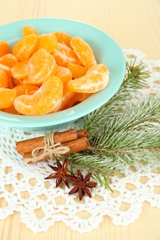 Ломтики вкусного мандарина на цветной тарелке на светлой поверхности