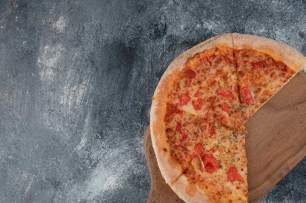 나무 절단 보드에 토마토와 함께 맛있는 마르게리타 피자.