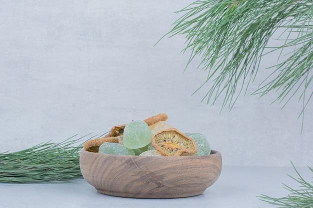 Вкусный мармелад и сушеные ломтики киви в деревянной миске.