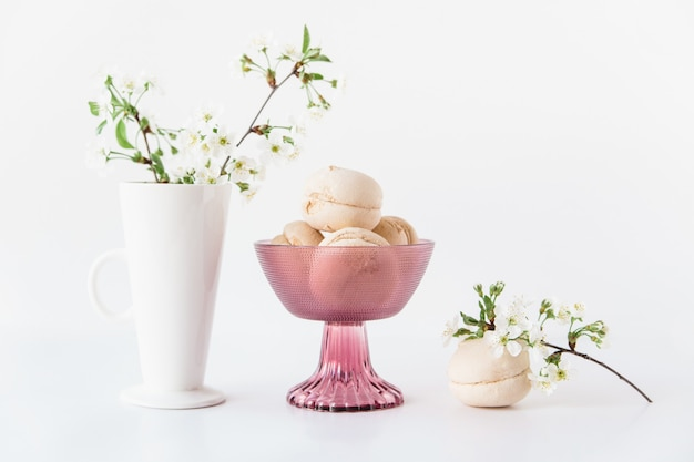 Tasty marshmallows in a pink glass vase and flowers in a white vase on white background