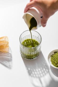 Вкусный чай маття, льющийся в стакан