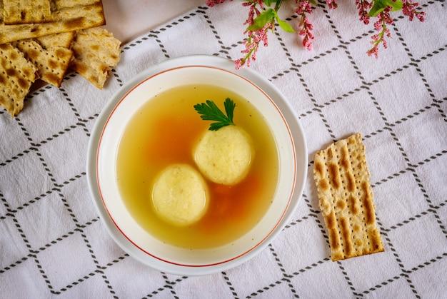Tasty matzo ball soup with carrot and matza bread.
