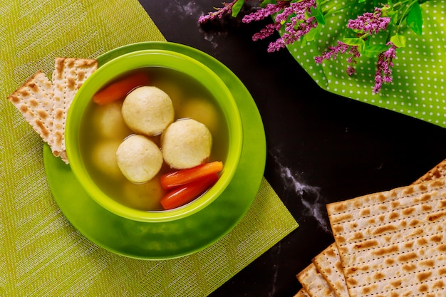 Tasty matzo ball soup with carrot and matzos bread. top view.