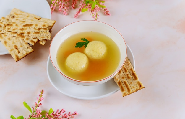 Tasty matzo ball soup with carrot and matzos bread.