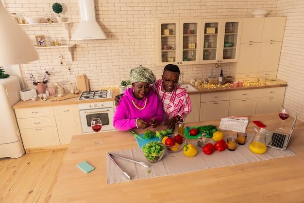 Вкусная еда. довольно радостная пара улыбается, наслаждаясь вместе готовить обед