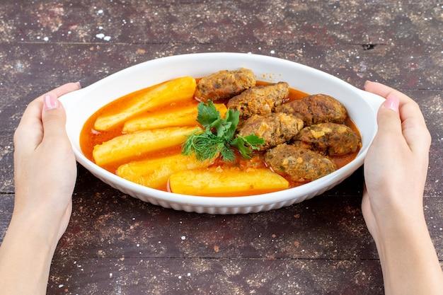 Вкусные мясные котлеты, приготовленные вместе с картофелем и соусом внутри тарелки, которую женщина принимает на коричневом столе