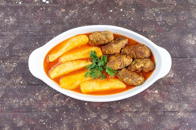 Вкусные мясные котлеты, приготовленные вместе с картофелем и соусом внутри тарелки с зеленью на коричневом