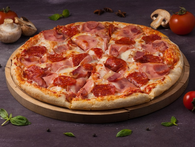 Tasty meat pizza with ham bacon and pepperoni on a wooden board