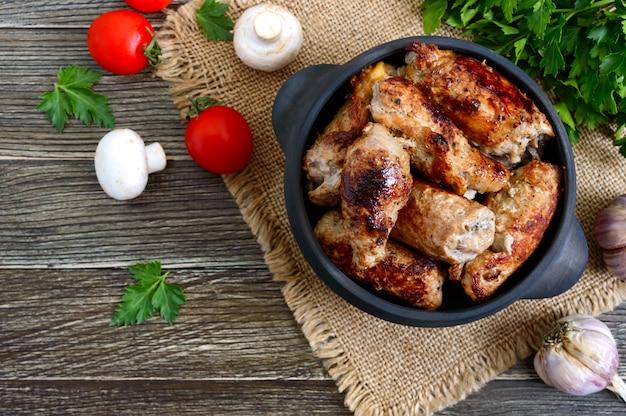 맛있는 고기 나무 테이블에 세라믹 냄비에 버섯과 롤. 평면도.