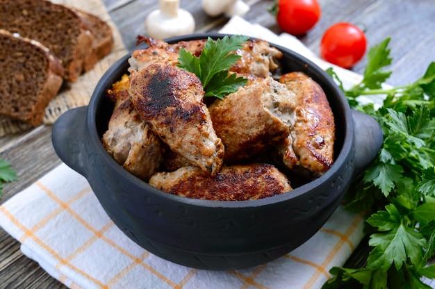 나무 테이블에 세라믹 냄비에 버섯과 맛있는 고기 롤