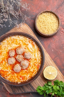 Tasty meatballs soup with noodles on board lemon wooden pasta a bunch of greens on dark background
