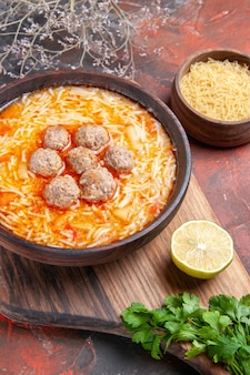 Tasty meatballs soup with noodles on board lemon wooden pasta a bunch of greens on dark table footage