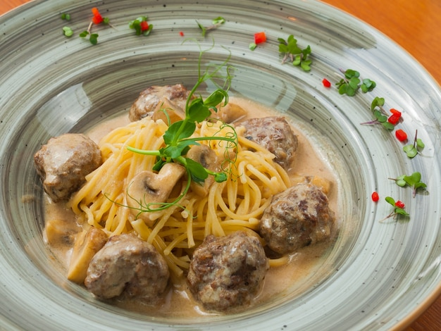 Tasty meatballs with spaghetti in creamy truffle sauce