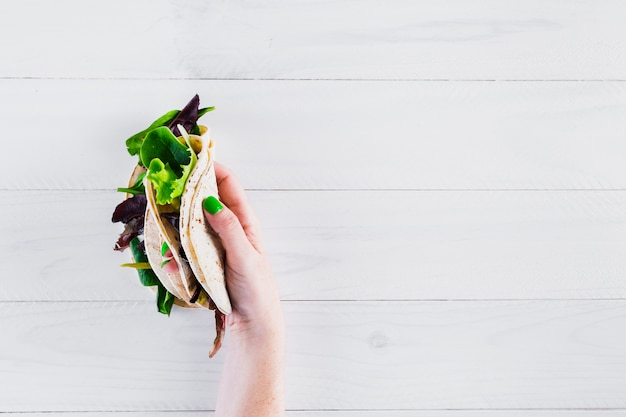 Tasty mexican burritos with hand